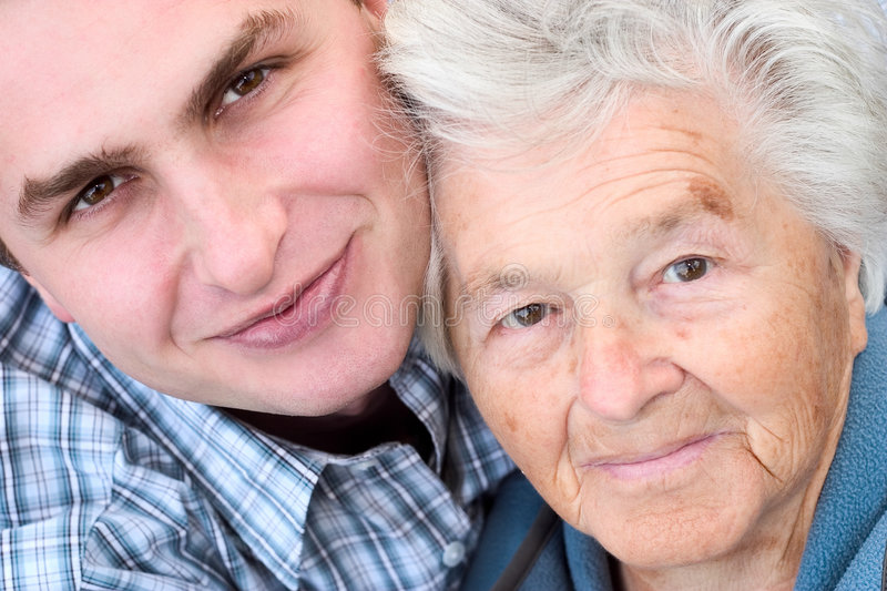 Elderly woman and young man stock photography