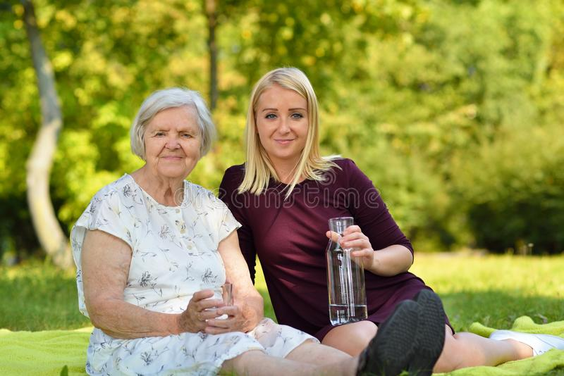 Elderly woman and young woman on grass. royalty free stock photography