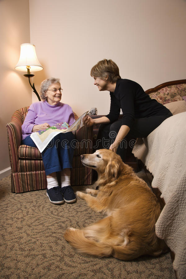 Elderly Woman With Younger Woman and Dog. Elderly Woman in her bedroom does needlepoint with a younger woman and a dog in the room. Vertical shot stock photos