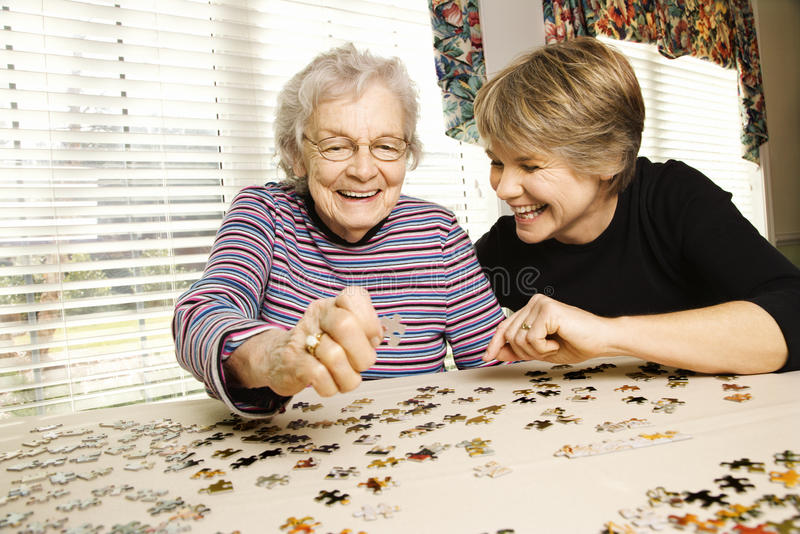 Elderly Woman And Younger Woman Doing Puzzle Royalty Free Stock Photography