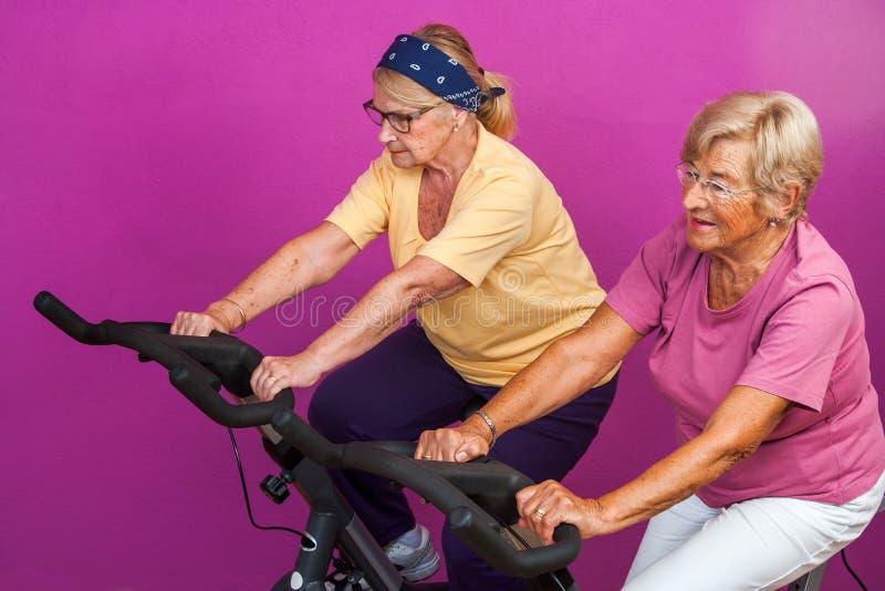 Elderly women doing leg exercises in gym. stock photography