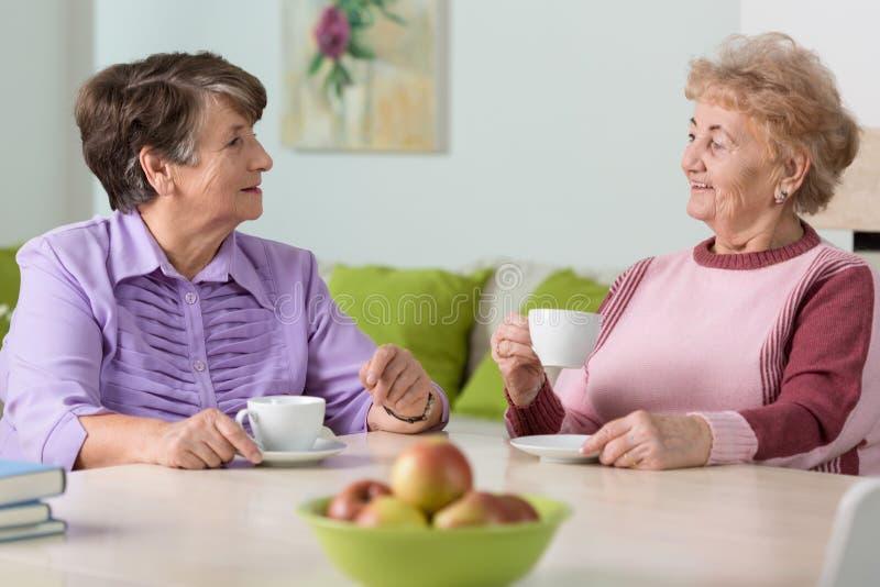 Elderly women drinking coffee royalty free stock photo
