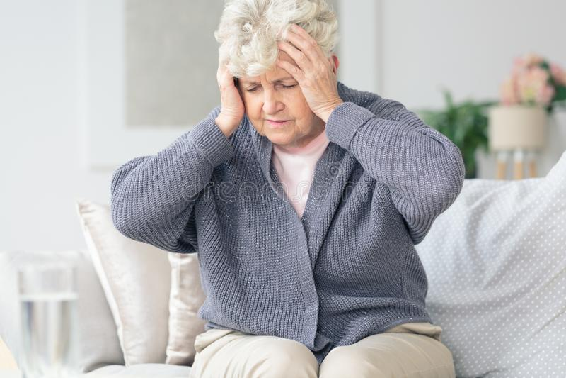 Elderly woman having migraine headache. Elderly women feeling sick holding head having painful migraine headache stock photo
