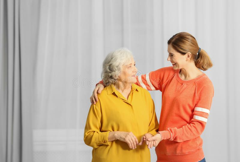 Elderly woman with female caregiver at home stock images