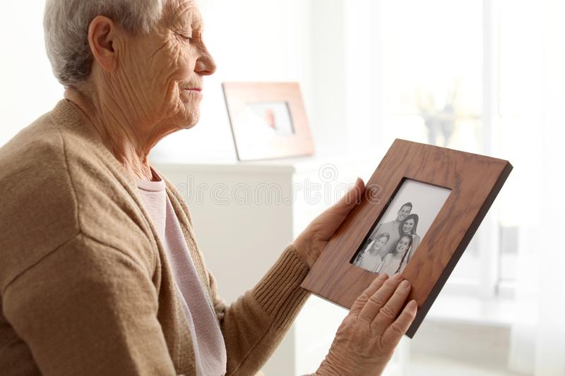 Elderly woman with framed family portrait at stock image