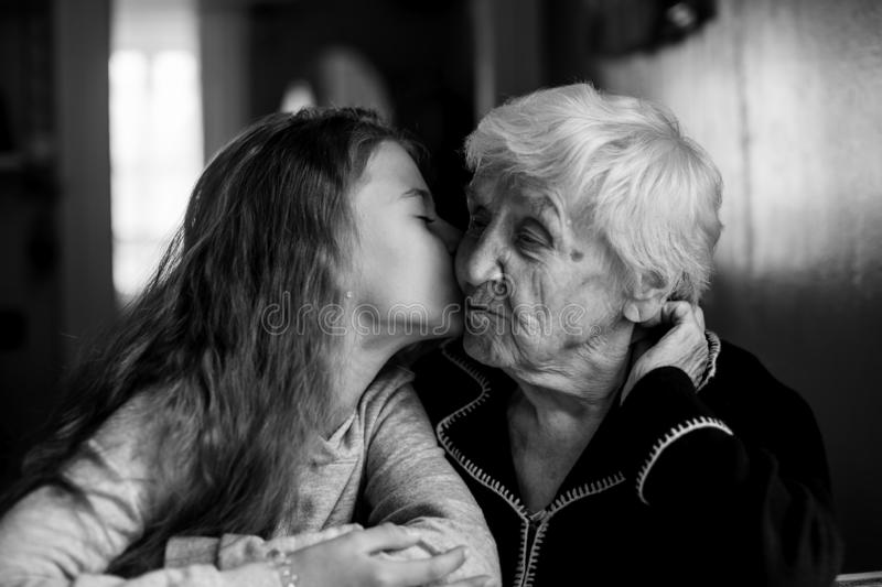 Elderly woman grandmother kiss with her little granddaughter. Elderly women grandmother kiss with her little granddaughter. Black and white photo stock photo