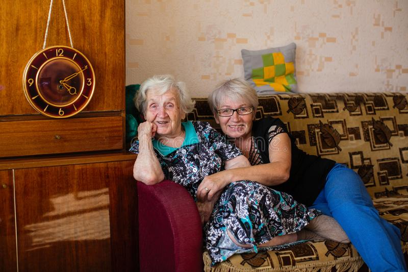 Elderly happy woman in home with his adult daughter posing for photos stock photo