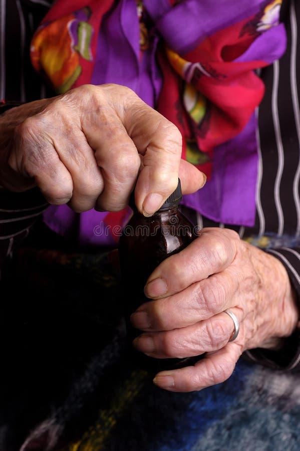 Elderly women opening medication bottle