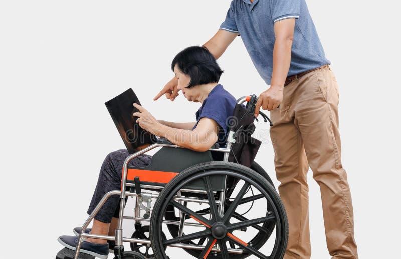Elderly woman reading a book on wheelchair with son take care. Elderly women reading a book on wheelchair with her son take care stock photos