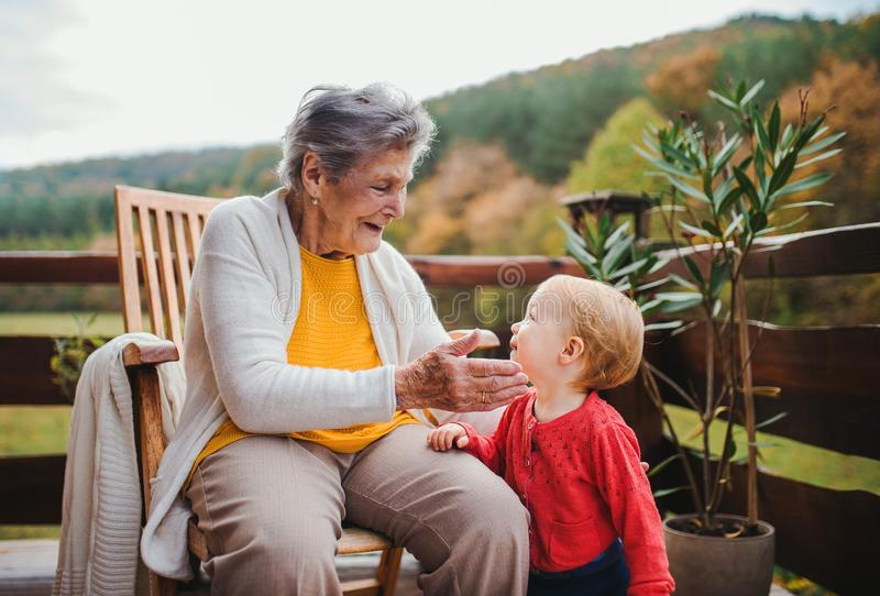 Elderly woman sitting with a toddler great-grandchild on a terrace in autumn. stock images
