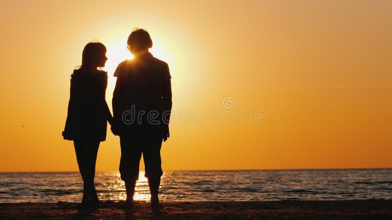 An elderly woman stands next to her granddaughter at sunset. Active seniors stock images