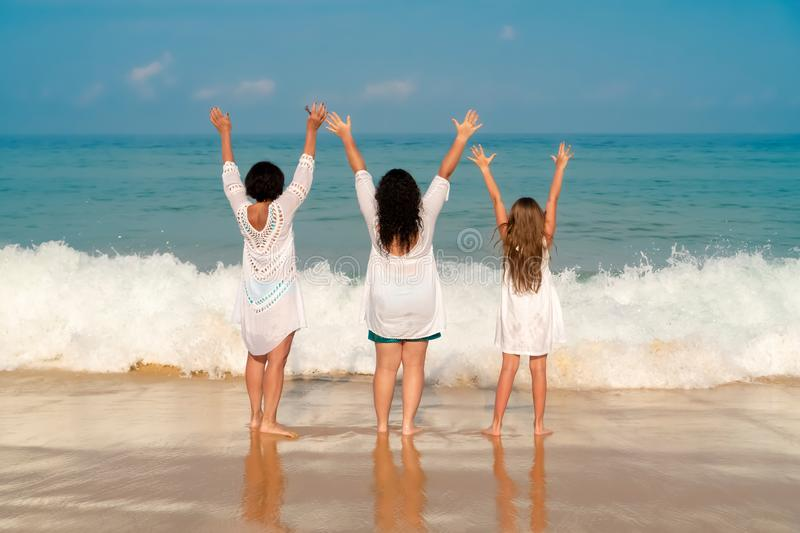 Grandmother, daughter and granddaughter raised their hands up on a sunny day. Concept of sunny and happy summer stock images