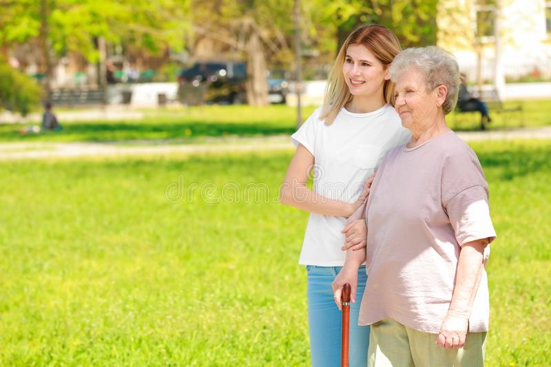 Elderly woman and young caregiver in park. Elderly women and young caregiver in park on sunny day stock image