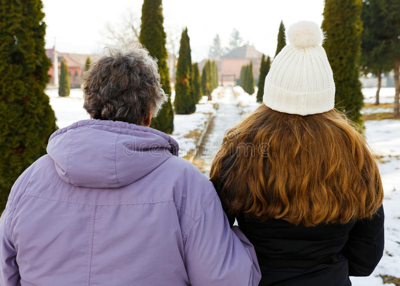 Elderly woman and young caregiver. Elderly women and young caregiver walking in the park in wintertime royalty free stock images