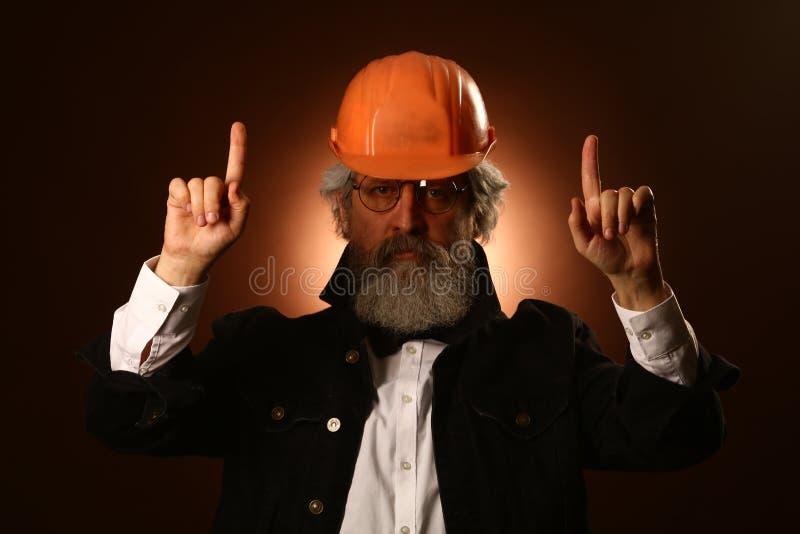 An elderly worker in a helmet gestures warning signs, studio portrait royalty free stock photo