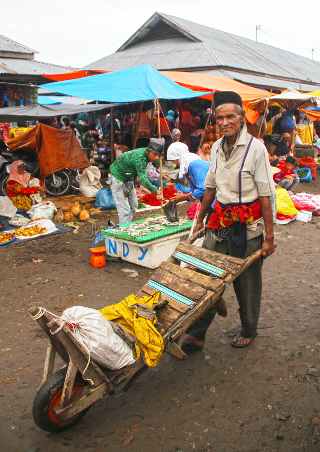 ELDERLY WORKER IN INDONESIA. An elderly man pushes a barrow after delivering vegetables, in a wet market in Padang City in West Sumatra, Indonesia royalty free stock photo