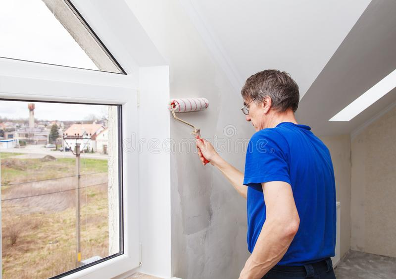 Elderly worker painting wall with glue. Elderly worker painting wall with background glue for a wallpaper stock photo