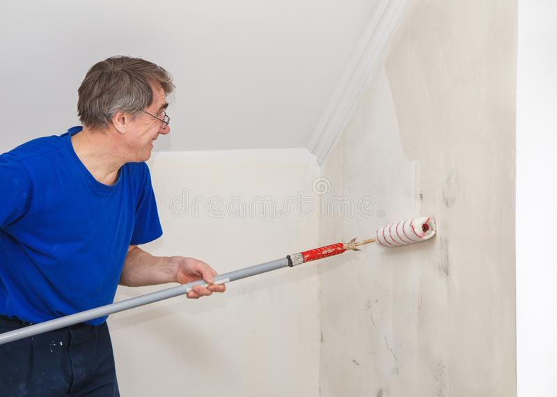 Elderly worker painting wall with glue. Elderly worker painting wall with background glue for a wallpaper royalty free stock photography