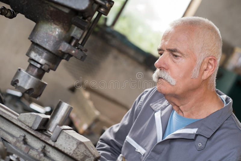 Elderly worker watches processing detail on milling machine. Elderly worker watches processing of detail on milling machine royalty free stock photo