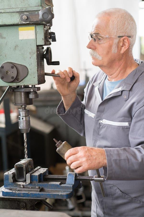 Elderly worker watches processing detail on milling machine. Elderly worker watches processing of detail on milling machine stock images