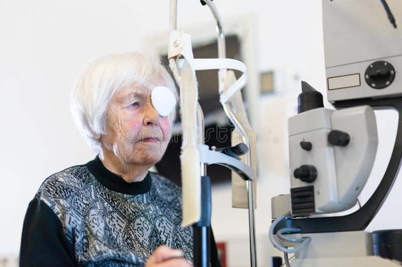 Senior woman wearing eye pathc after laser surgery procedure at ophthalmology clinic. Elderly 95 years old woman wearing eye pathc after laser surgery procedure stock images