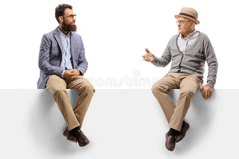 Elderly and younger man sitting on a panel and talking royalty free stock image