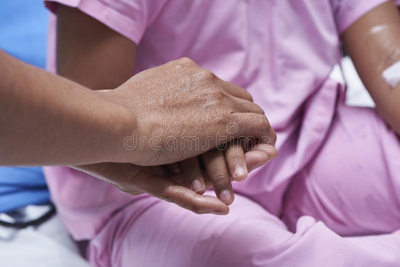 Family holding patient hand for sympathy. Eldery family holding young patient hand for giving sympathy in hospital stock photography