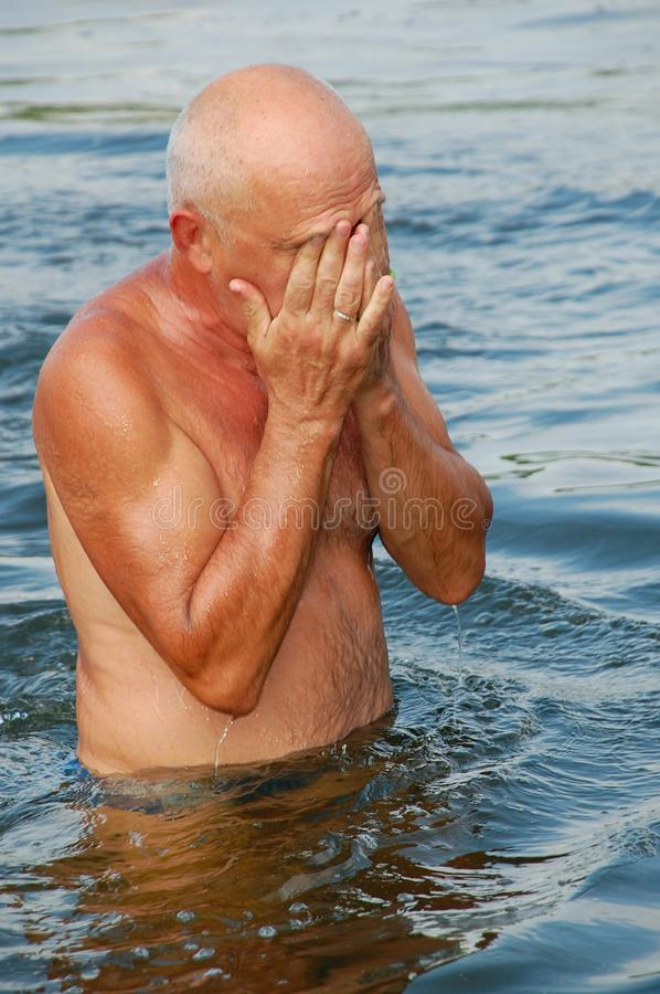 Eldery man in water stock photography