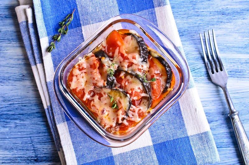 Eldfast form av aubergine och tomaten med ost royaltyfri bild