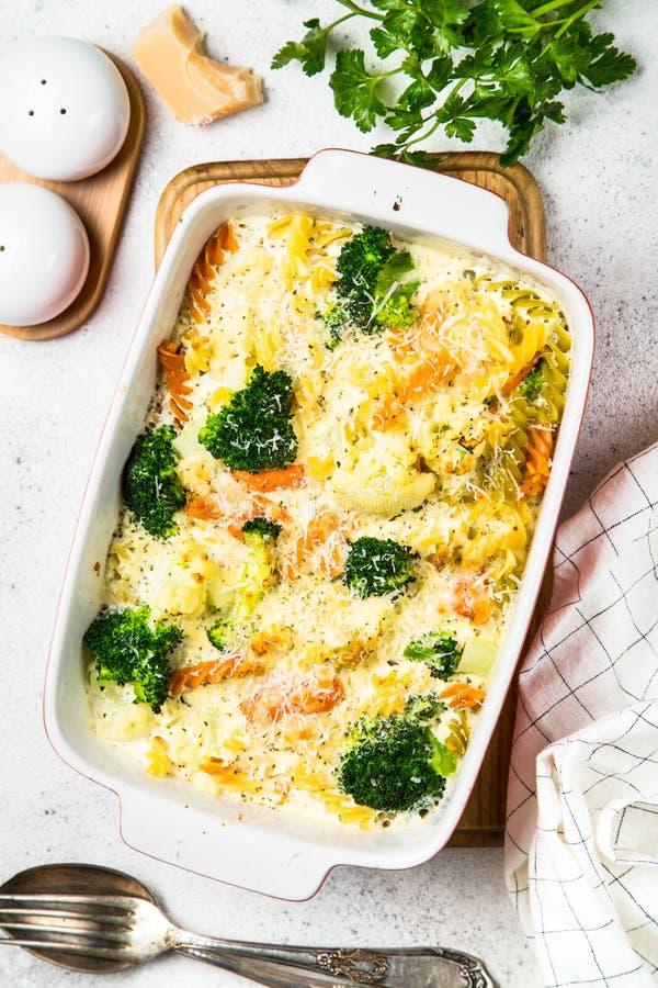 Eldfast form från pasta och grönsaker, i att baka maträtten arkivbild