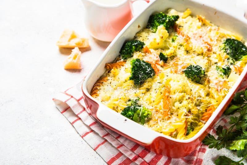 Eldfast form från pasta och grönsaker, i att baka maträtten arkivfoton