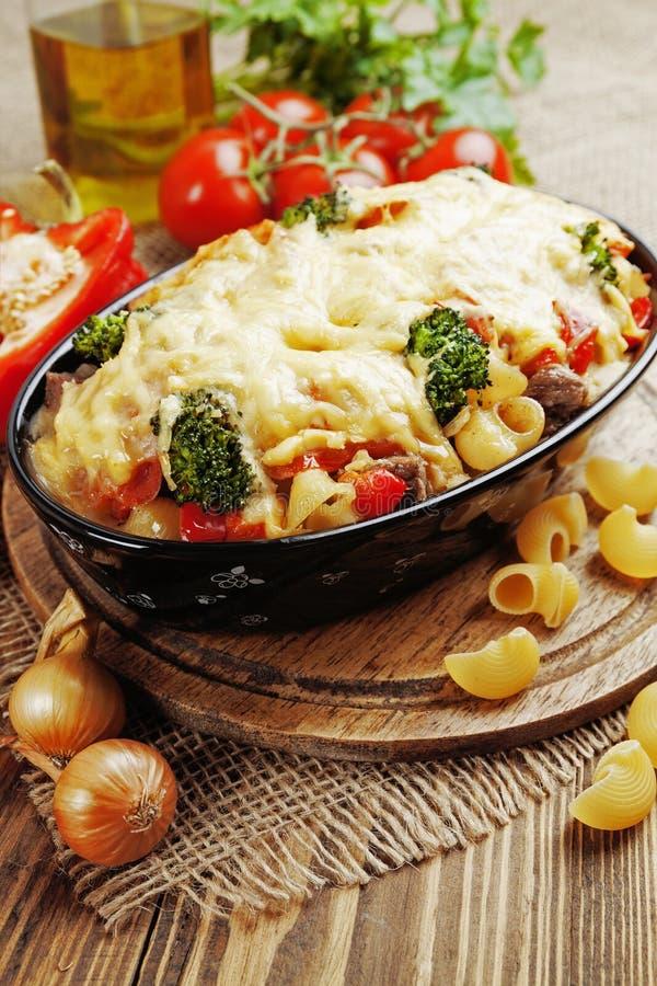 Eldfast form med kött, pasta, broccoli och tomater royaltyfria bilder