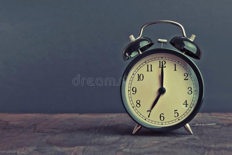 Ele pulso de disparo do ` do ` s sete o já, hora de acordar para o café da manhã, despertador metálico preto velho do vintage imagem de stock