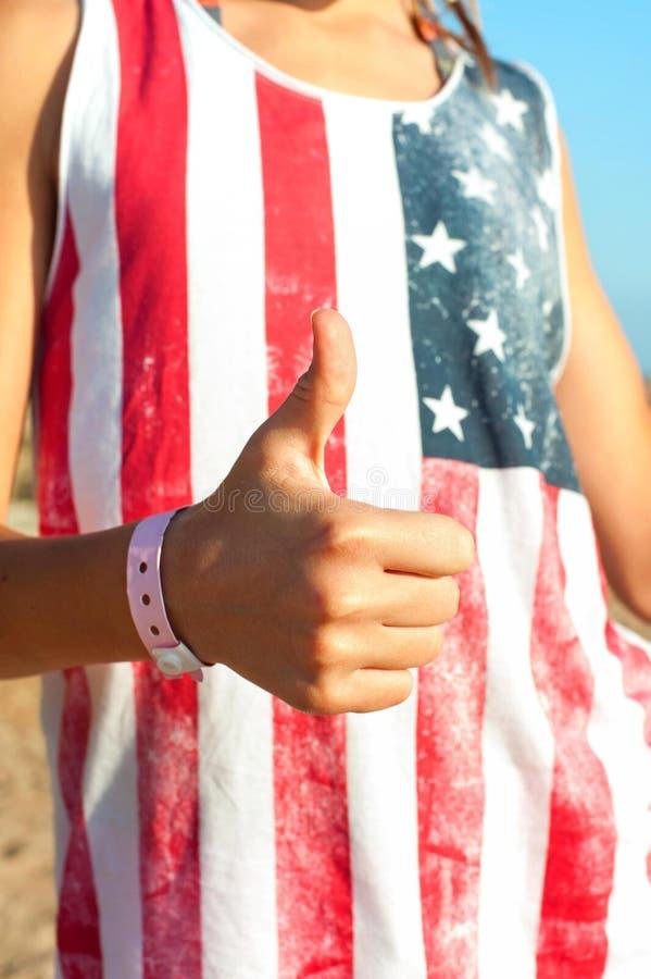 Ele ` s bem! Moça na camisa americana que mostra o polegar acima imagens de stock