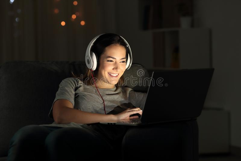 Elearning feliz de la muchacha en línea con un ordenador portátil en la noche fotografía de archivo libre de regalías