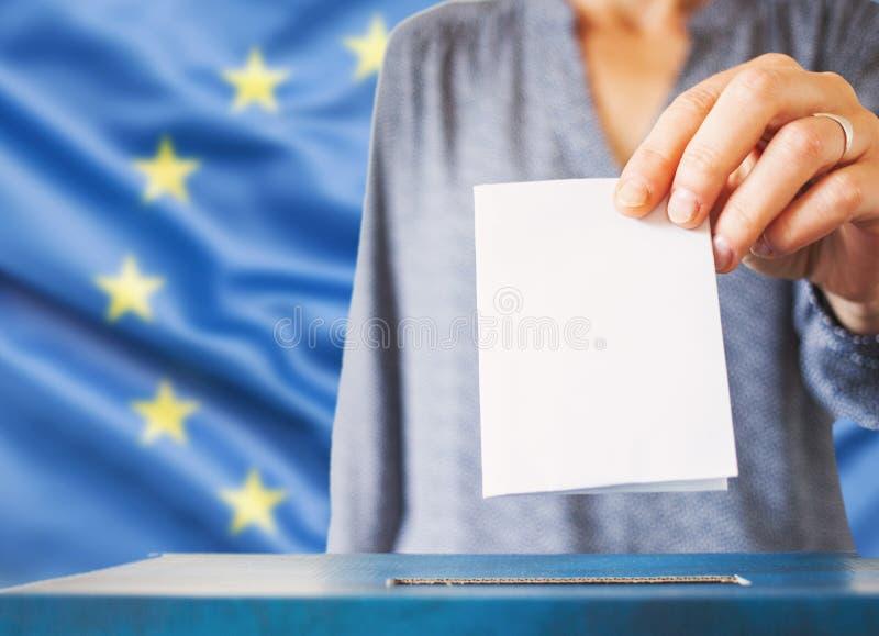 elecciones en la Unión Europea La mano de la mujer que pone su voto en las urnas Bandera de la UE en segundo plano foto de archivo