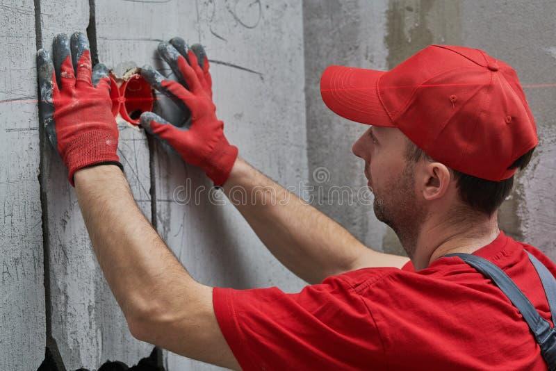 Elecrician arbete Installation av elektriskt uttag för vägg med laser-nivån royaltyfri foto