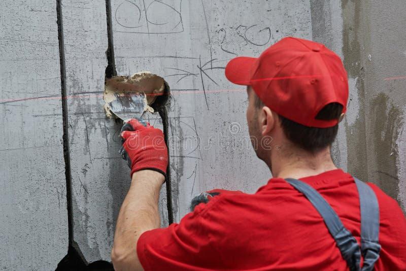 Elecrician arbete Installation av elektriskt uttag för vägg med laser-nivån arkivfoto