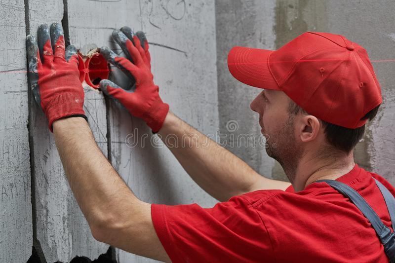 Elecrician work. Installing wall electric outlet with laser level. Elecrician work. Installing wall electric outlet box for internal electricity cable with laser royalty free stock photo