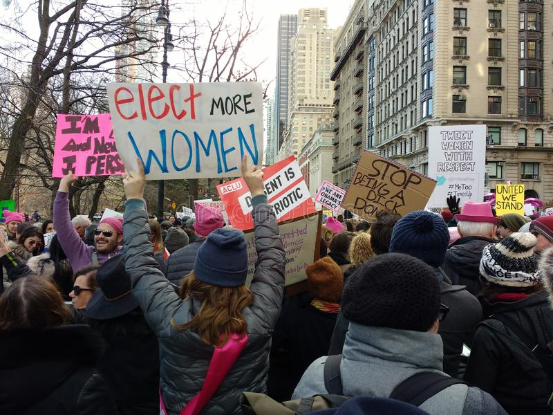 Elect Women, Women`s March, NYC, NY, USA. Among the Women`s March crowd marching down Central Park West, a demonstrator holds a sign that says, `Elect More Women royalty free stock images