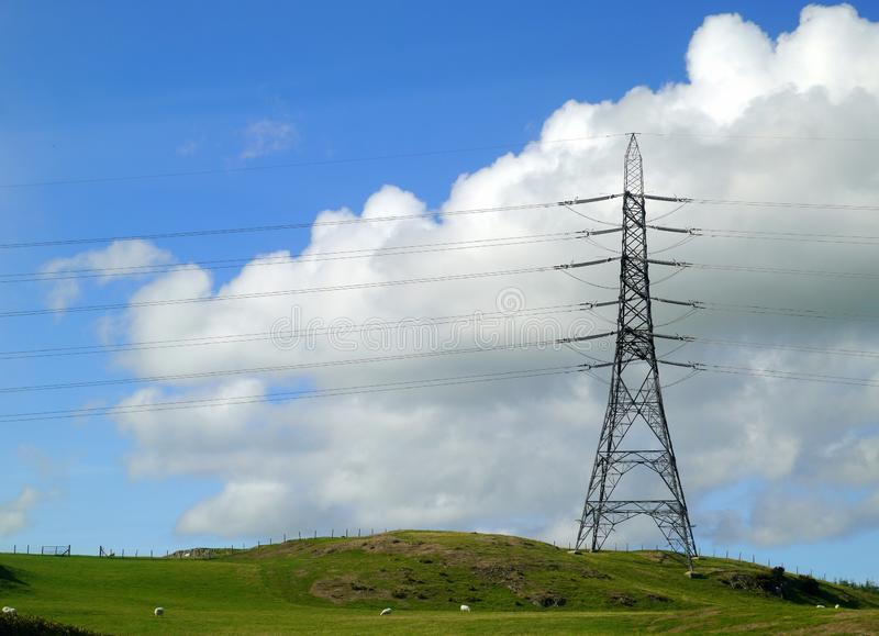 Electicity pylon on hillside. An electricity pylon on a hillside , against rolling clouds and blue skies stock photos