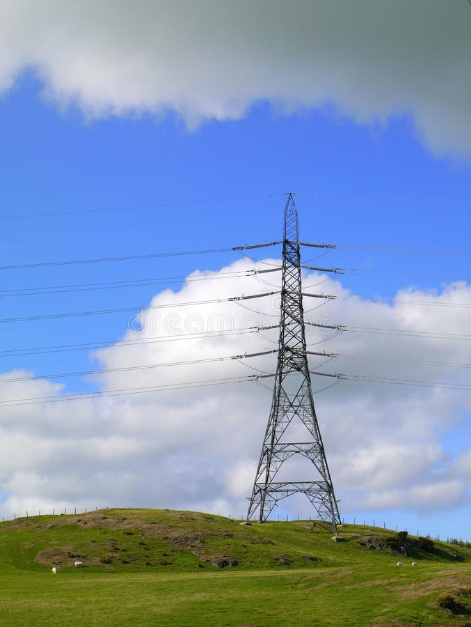 Electicity pylon on hillside. An electricity pylon on a hillside , and beneath a symbolic grey cloud royalty free stock images