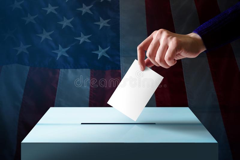Election in America Concept. Hand Dropping a Ballot Card into th royalty free stock photos