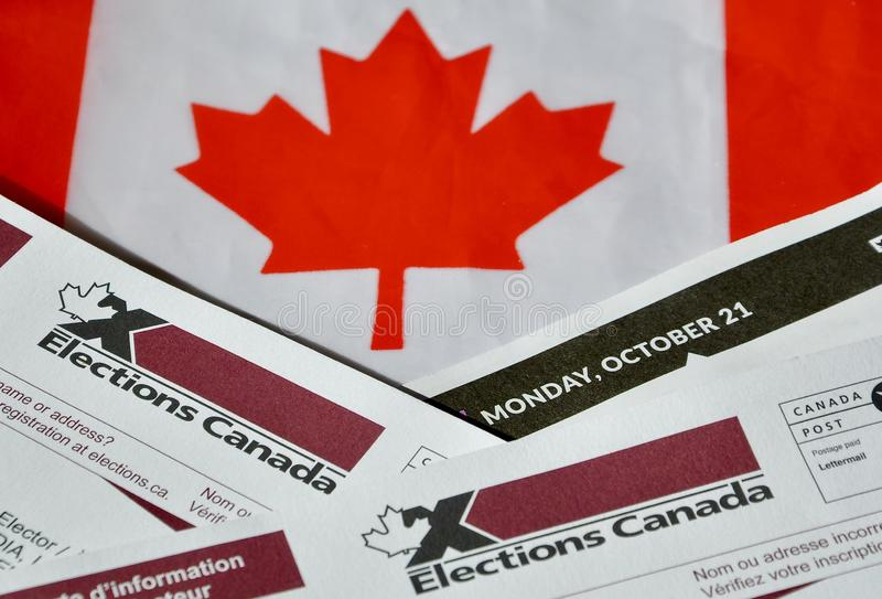 Election Canada voter information cards over small Canadian flag. As a symbol of federal election this coming October 21, 2019 stock photo