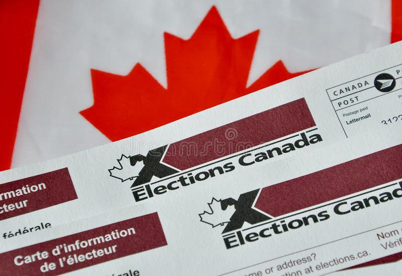 Election Canada voter information cards over small Canadian flag. As a symbol of federal election this coming October 21, 2019 stock photos