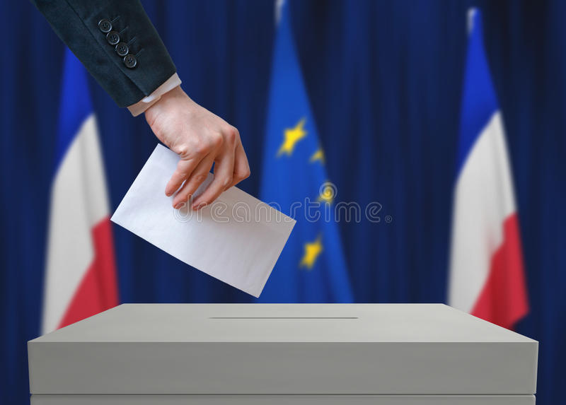 Election in France. Voter holds envelope in hand above vote ballot. royalty free stock image