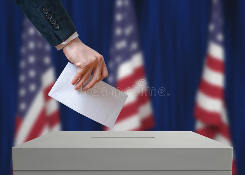 Election in United States of America. Voter holds envelope in hand above vote ballot. royalty free stock photos