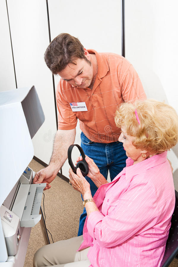 Election Volunteer. Helps a hearing impaired senior women vote on a touch screen machine using headphones stock image