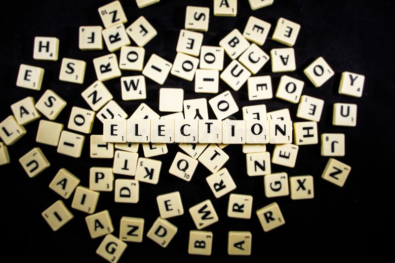 Election word spelled with letter tiles in black background stock photo