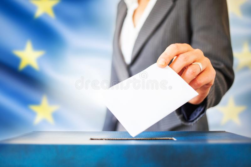 Elections in European Union. The hand of woman putting her vote in the ballot box. EU flag in the background. Elections in European Union. The hand of woman royalty free stock photos
